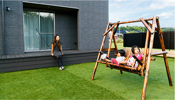 庭で木製ブランコにのる女の子2人と、笑顔のお母さん